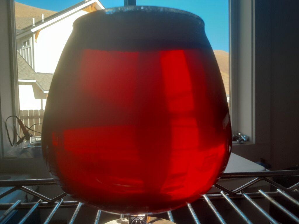Amber ale backlit by garage window